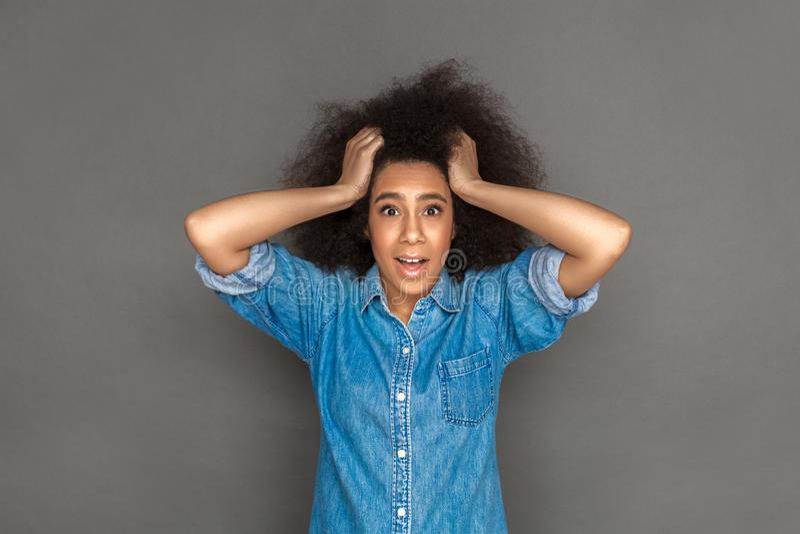 freistil Mulattefrauenstellung lokalisiert auf dem grauen haltenen Haar, welches die Kamera überrascht schaut lizenzfreie stockfotografie