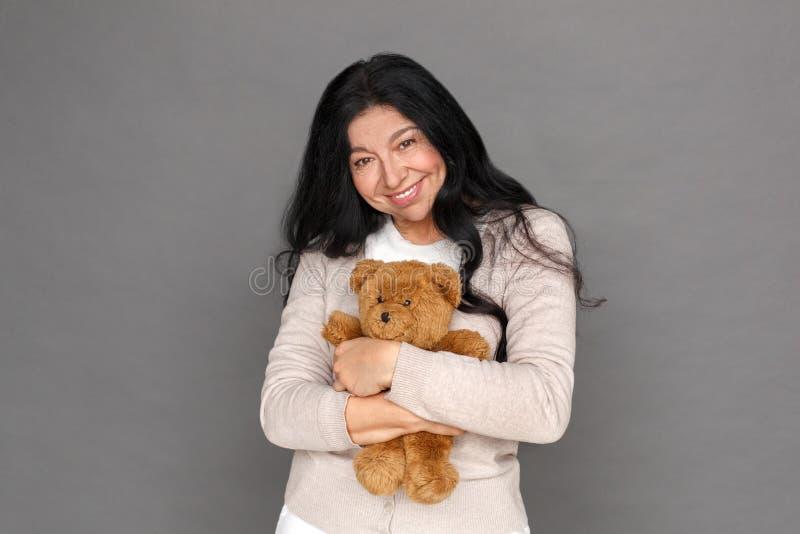 freistil Reife Damenstellung auf dem grauen umarmenden Teddybären, der die Kamera nett schaut stockfoto