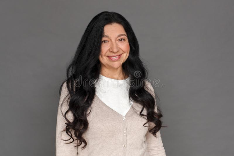 freistil Reife Damenstellung lokalisiert auf dem grauen Lächeln glücklich lizenzfreies stockfoto
