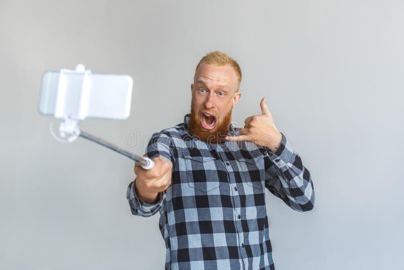 freistil Reife Mannstellung lokalisiert auf Grau mit dem monopod, das selfie auf dem Smartphonevertretungsanruf-Gestenschreien ni lizenzfreie stockbilder