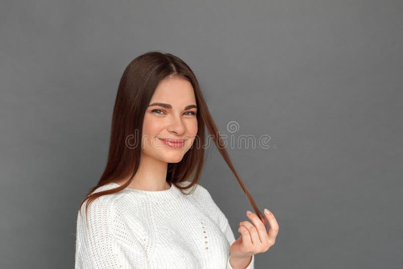 freistil Stellung des jungen Mädchens auf dem grauen Spielen mit lächelnder glücklicher Nahaufnahme des Haares stockbilder