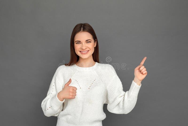freistil Stellung des jungen Mädchens auf grauem auf Daumen des Raumes herauf das Lächeln beiseite zeigen glücklich lizenzfreies stockbild
