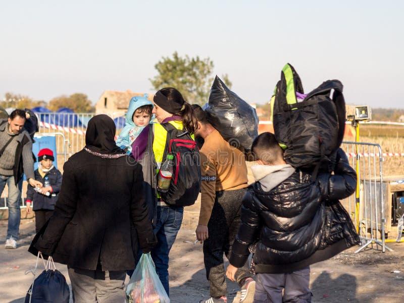 Freiwillig, ein Baby tragend, umgeben von den Flüchtlingen, die in Richtung zur Grenze Kroatiens Serbien, zwischen Städte von Bap stockbild