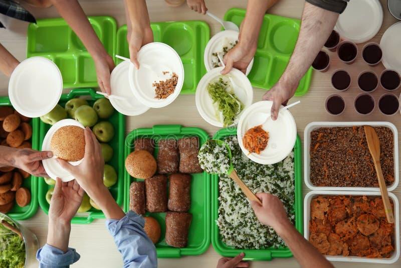 Freiwillige, die bei Tisch Lebensmittel für arme Leute dienen stockfotos