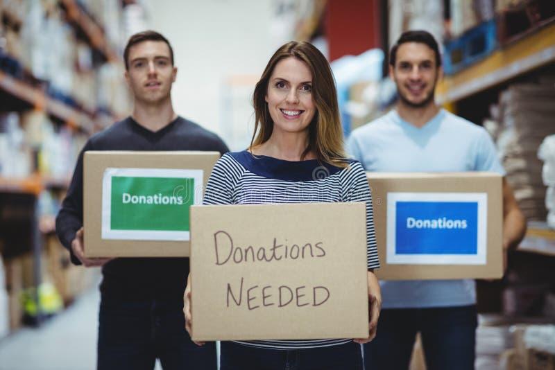 Freiwillige, die an der Kamera hält Spendenkästen lächeln lizenzfreie stockfotografie