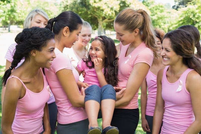 Freiwillige, die Mädchen während der Brustkrebskampagne tragen stockfoto