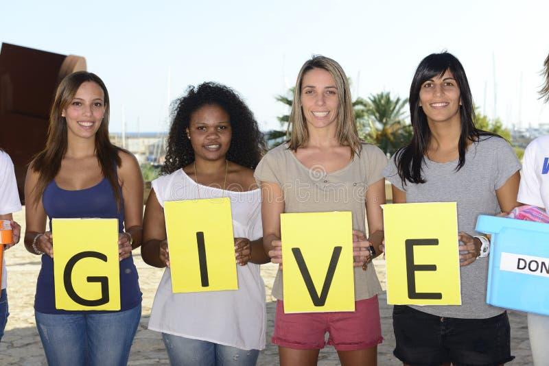 Freiwillige Gruppe mit Zeichen geben stockbild