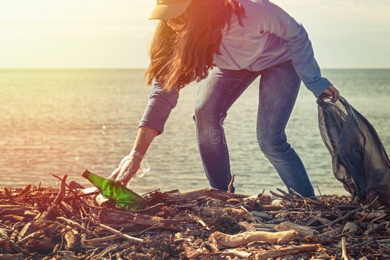 Freiwillige Hilfen der Frau den Strand des Abfalls s?ubern Tag der Erde und Verbesserung der Umwelts-Konzept ?kologie und Sicherh stockfotografie