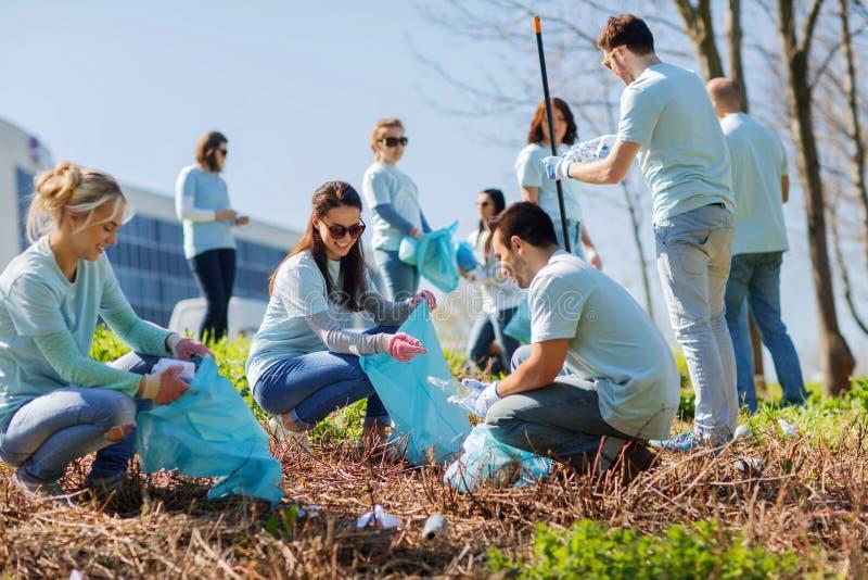 Freiwillige mit den Abfalltaschen, die Parkbereich säubern lizenzfreies stockfoto