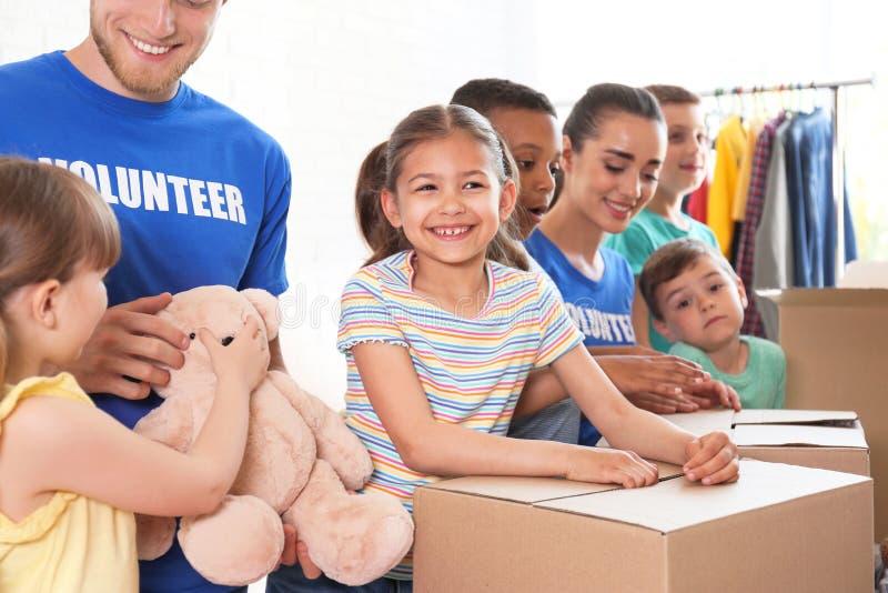 Freiwillige mit den Kindern, die Spendenwaren sortieren stockfotografie