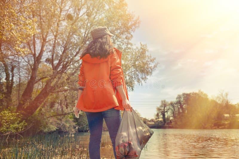 Freiwillige Stellung der Frau auf der Flussbank mit einer Tasche des Abfalls Das Konzept der Umweltverschmutzung R?ckseitige Ansi stockfotografie