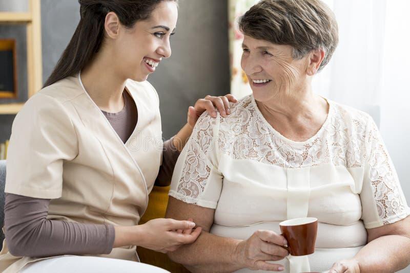 Freiwillige Unterhaltung mit Senior lizenzfreies stockbild