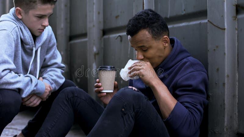 Freiwilliger behandelnder afroer-amerikanisch Obdachloser mit dem freiem Mittagessen, Güte und Nächstenliebe lizenzfreie stockfotografie
