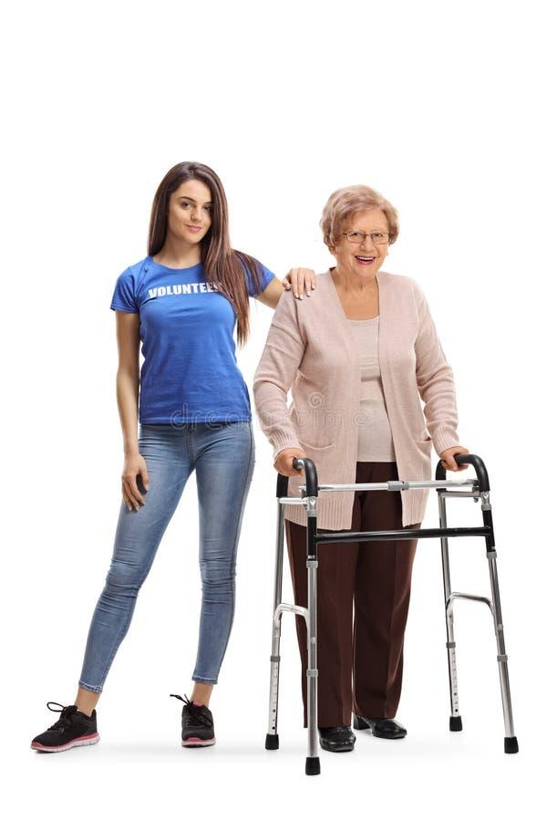 Freiwilliger der jungen Frau, welche einer älteren Dame mit einem Wanderer hilft lizenzfreie stockfotos