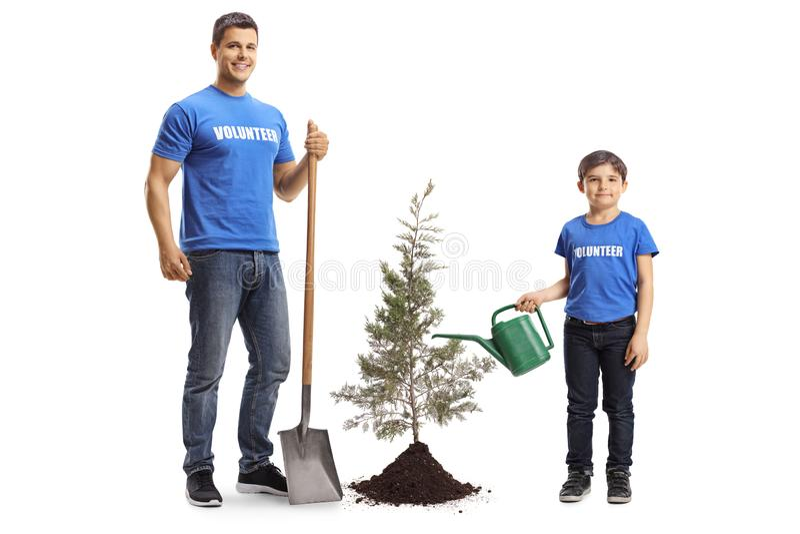 Freiwilliger des jungen Mannes mit einer Schaufel und ein Jungenfreiwilliger, der einen Baum wässert lizenzfreie stockfotografie