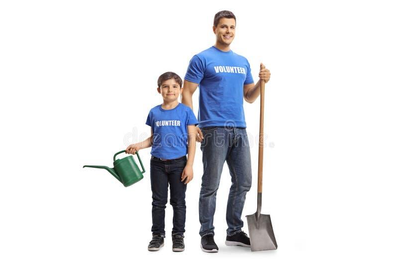 Freiwilliger des jungen Mannes mit einer Schaufel und einem männlichen Kind mit einem Bewässerungstopf stockfotografie