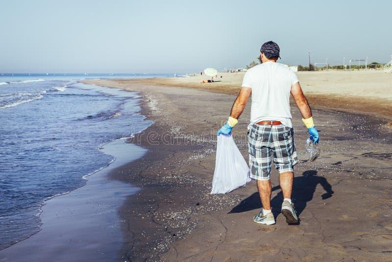 Freiwilliger des Sammelns Abfall oben, das das Meer verunreinigen lizenzfreies stockbild