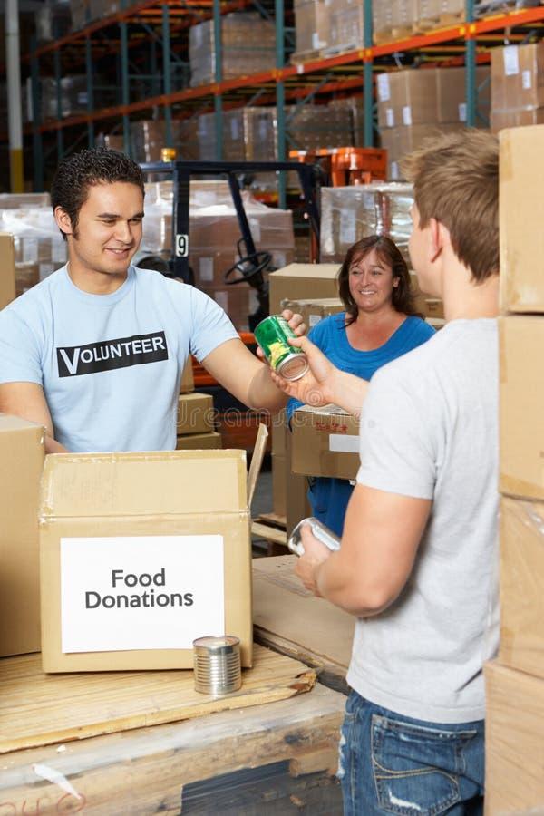 Freiwilliger, die Nahrungsmittelabgaben im Lager montieren stockfotos