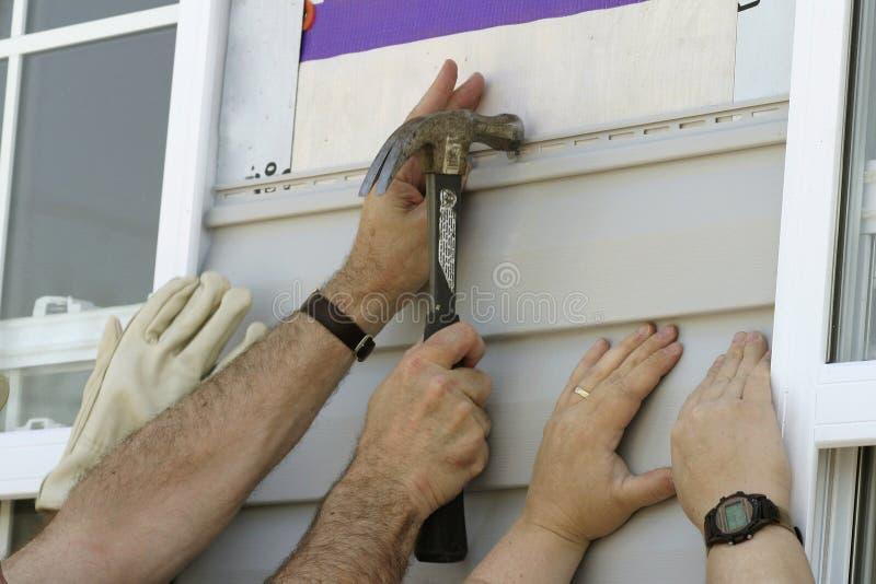 Freiwilliger, die Sidiing auf ein neues Haus installieren stockbilder