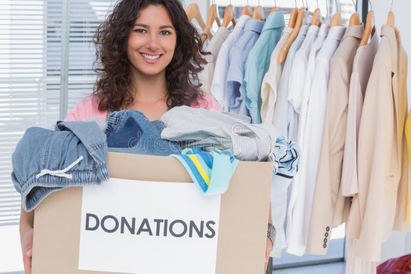 Freiwilliger haltener Kleidungsspendenkasten stockbilder