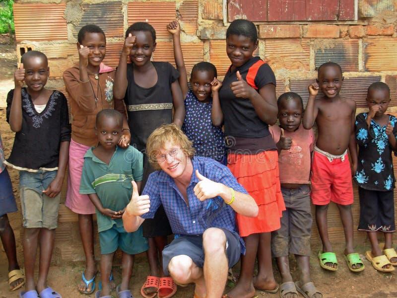 Freiwilliger Hilfsmitarbeiter einer hilfsorganisation, der den Spaß oben beibringt afrikanischen Kindern Daumen hat stockfotos