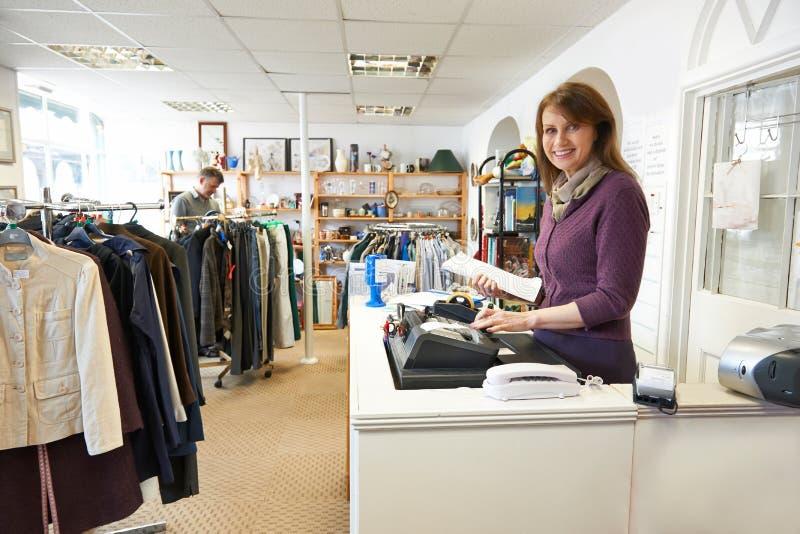 Freiwilliger im Nächstenliebe-Shop mit Kunden lizenzfreies stockfoto