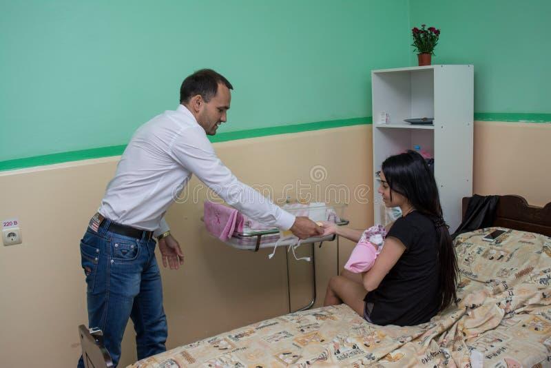 Freiwilliger Mann, der Kleidung für Babys in der Geburtsklinik während des Kinderschutztages spendet stockbild