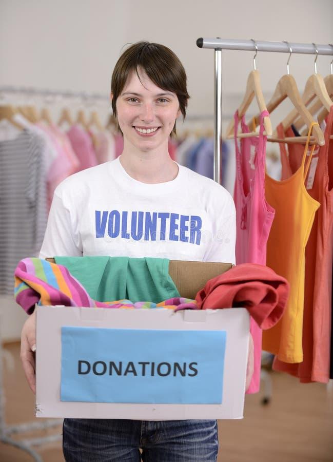 Freiwilliger mit Kleidungabgabekasten stockfotos