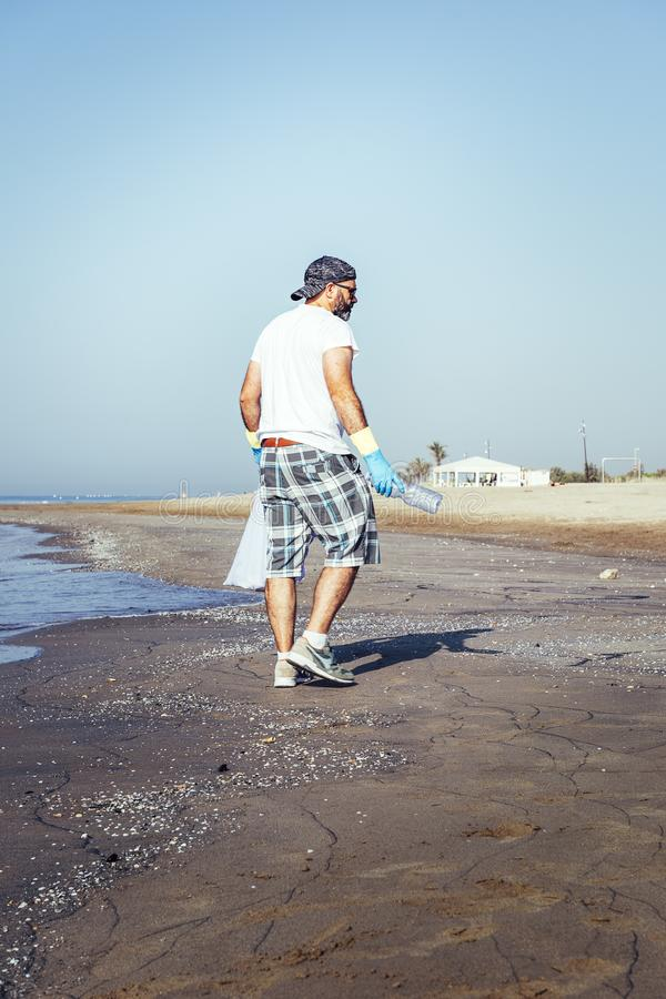 Freiwilliger sammelnder Abfall, das den Strand verunreinigen stockfotos