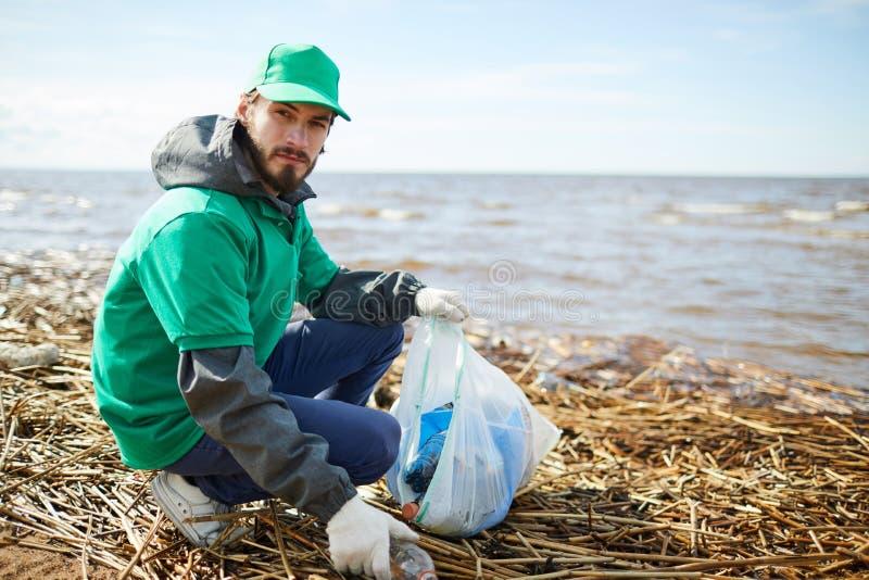 Freiwilliger setzender Abfall zur Tasche und Betrachten der Kamera lizenzfreie stockfotografie