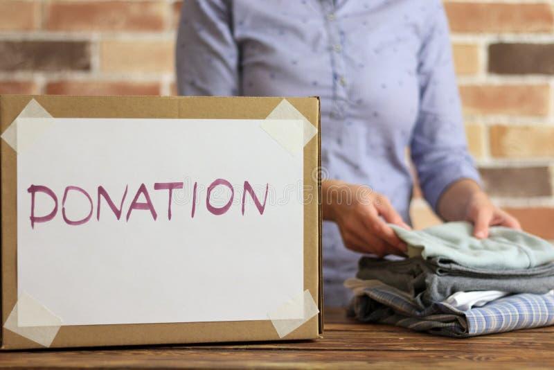 Freiwilliger setzt Kleidung zur Pappschachtel für Spende stockfotografie