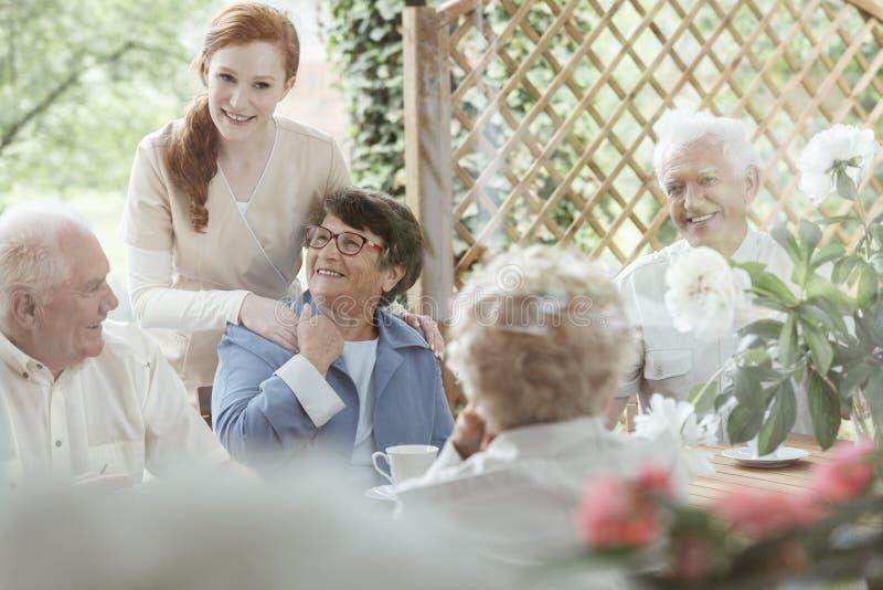 Freiwilliger stützt eine ältere Frau stockfotos