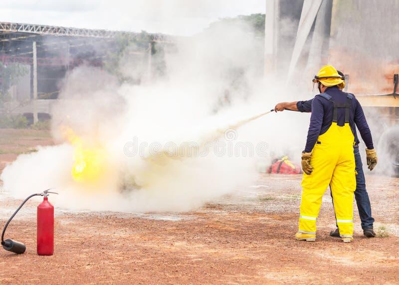 Freiwilliger unter Verwendung des Feuerlöschers vom Schlauch für die Feuerbekämpfung während der grundlegenden Ausbildungsevakuie stockfotografie