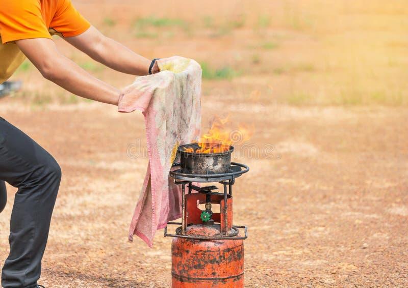Freiwilliger unter Verwendung des nass Stoffes oder feuchter Stoff schlugen die Flamme heraus während des grundlegenden Feuerbekä stockfoto