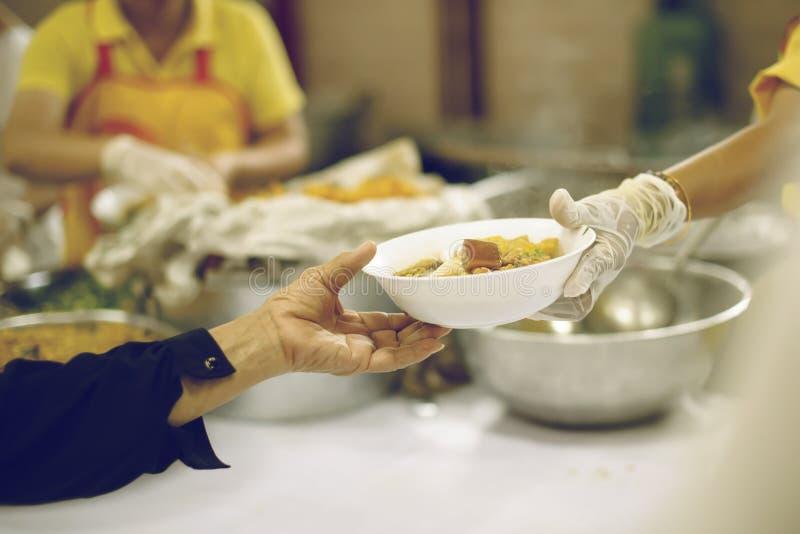 Freiwilliger, zum das hungrige in der Gesellschaft einzuziehen: Das Konzept des Spendens der Nahrung zu den Armen in der Gesellsc stockfotografie