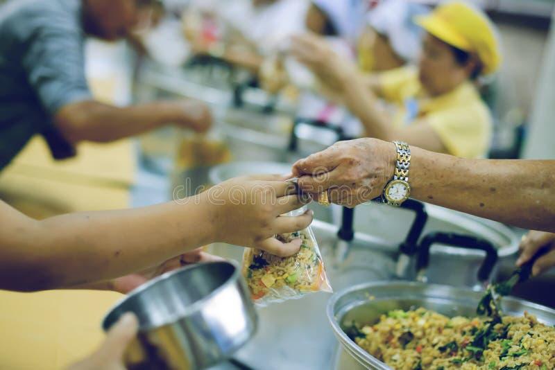 Freiwilliger, zum das hungrige in der Gesellschaft einzuziehen: Das Konzept des Spendens der Nahrung zu den Armen in der Gesellsc stockbild