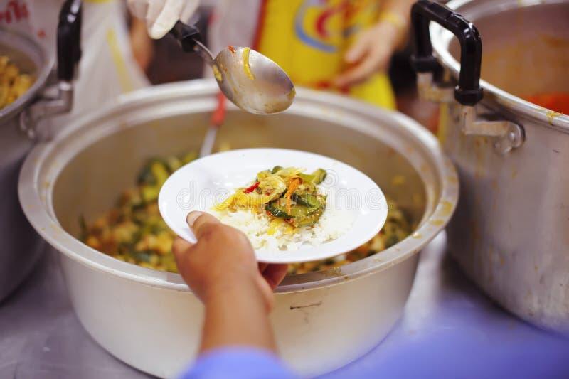Freiwilliger, zum das hungrige in der Gesellschaft einzuziehen: Das Konzept des Spendens der Nahrung zu den Armen in der Gesellsc stockfoto