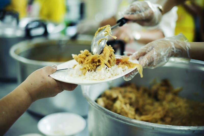 Freiwilliger, zum das hungrige in der Gesellschaft einzuziehen: Das Konzept des Spendens der Nahrung zu den Armen in der Gesellsc lizenzfreie stockfotografie