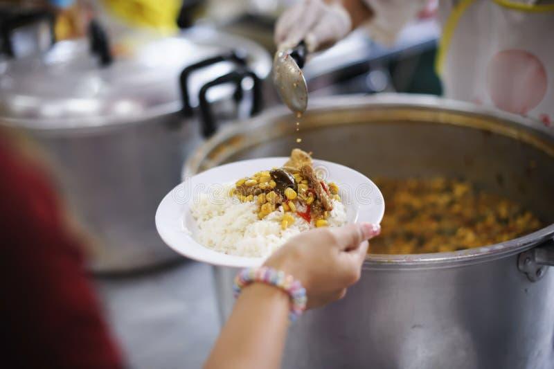 Freiwilliger, zum das hungrige in der Gesellschaft einzuziehen: Das Konzept des Spendens der Nahrung zu den Armen in der Gesellsc lizenzfreies stockbild
