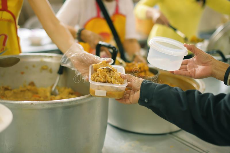 Freiwilliger, zum das hungrige in der Gesellschaft einzuziehen: Das Konzept des Spendens der Nahrung zu den Armen in der Gesellsc stockbilder