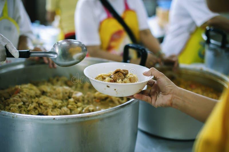 Freiwilliger, zum das hungrige in der Gesellschaft einzuziehen: Das Konzept des Spendens der Nahrung zu den Armen in der Gesellsc lizenzfreie stockfotos