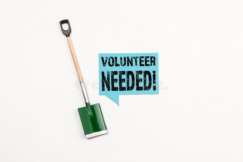 Freiwilliges erforderliches Konzept, Schaufel für das Graben und Zeichen mit Text lizenzfreie stockbilder