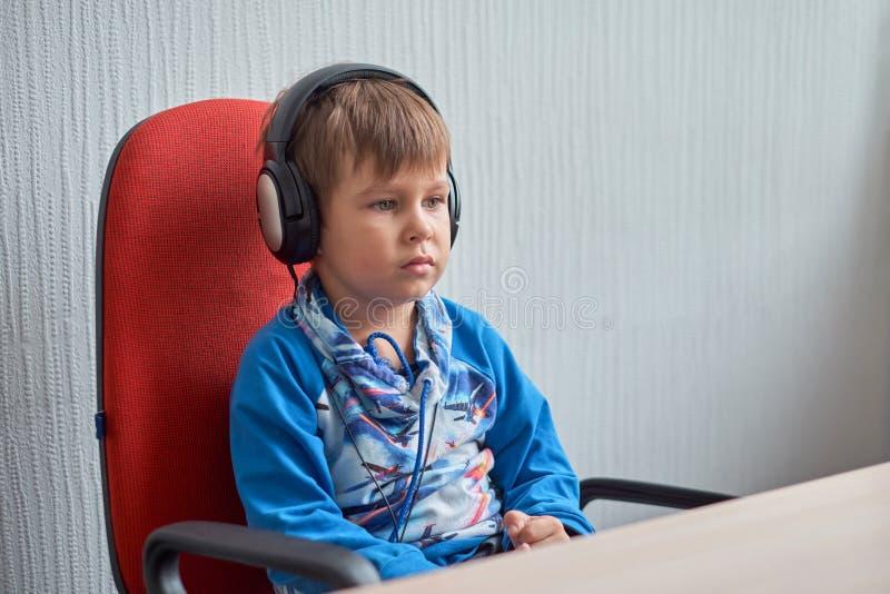Freizeit, Bildung, Kinder, Technologie und Leutekonzept - Junge mit Computer und Kopfhörern im Büro lizenzfreies stockfoto