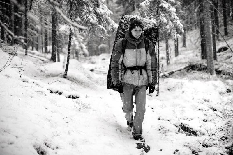 Freizeit des Winters im Freien Berufskletterer mit einer Abbruchsauflage auf seinem zurück in einem schneebedeckten Wald, Extreem stockbild