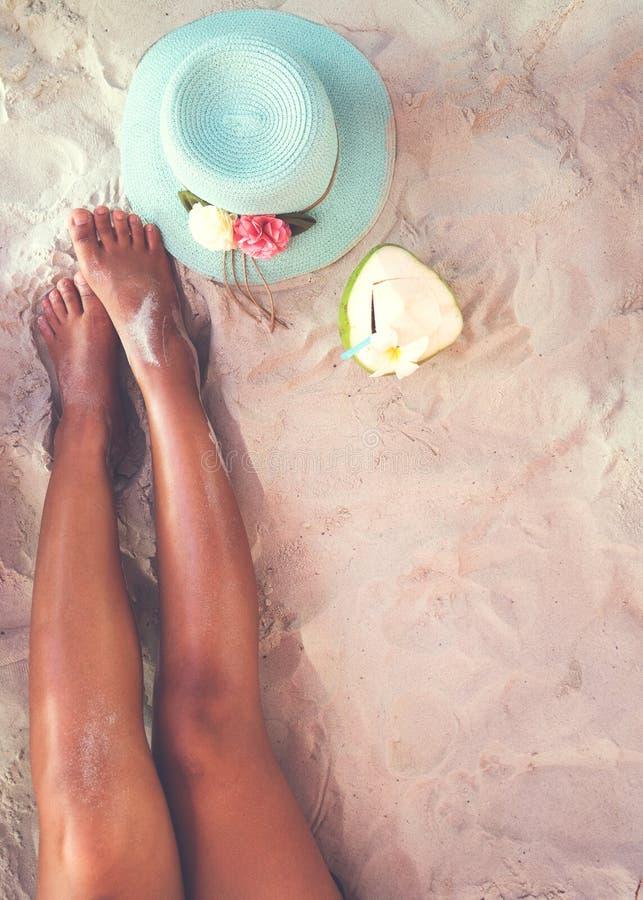 Freizeit im Sommer -, der von den sexy Frauen schön ist, bräunen Sie sich entspannen Sie sich auf sandigem Strand mit Hut- und Ko lizenzfreies stockbild