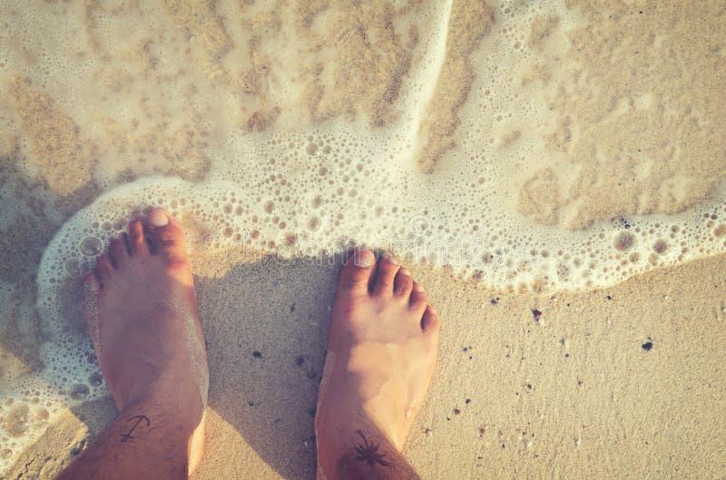 Freizeit im Sommer entspannen sich auf Strand - oben von Mann ` s Fuß mit Tätowierung lizenzfreies stockfoto