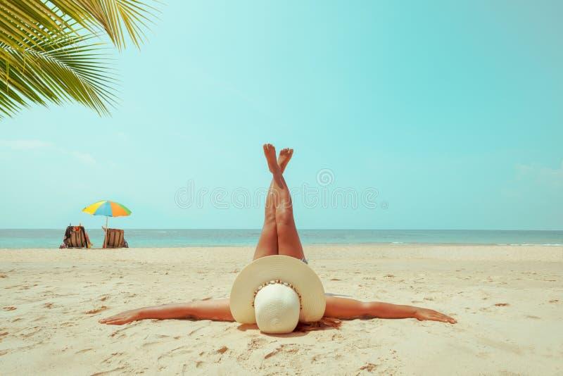 Freizeit im Sommer - junge Frau im liegenden Strohhut, auf einem tropischen Strand ein Sonnenbad zu nehmen lizenzfreie stockfotografie