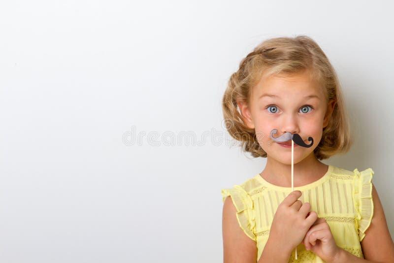 Freizeit zum Spaß Schließen Sie herauf kleines Mädchen des Porträts mit dem gefälschten Schnurrbart mit prallem stockfotografie