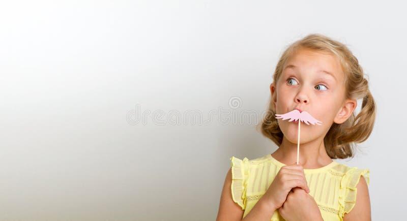 Freizeit zum Spaß Schließen Sie herauf kleines Mädchen des Porträts mit dem gefälschten Schnurrbart mit prallem stockbilder