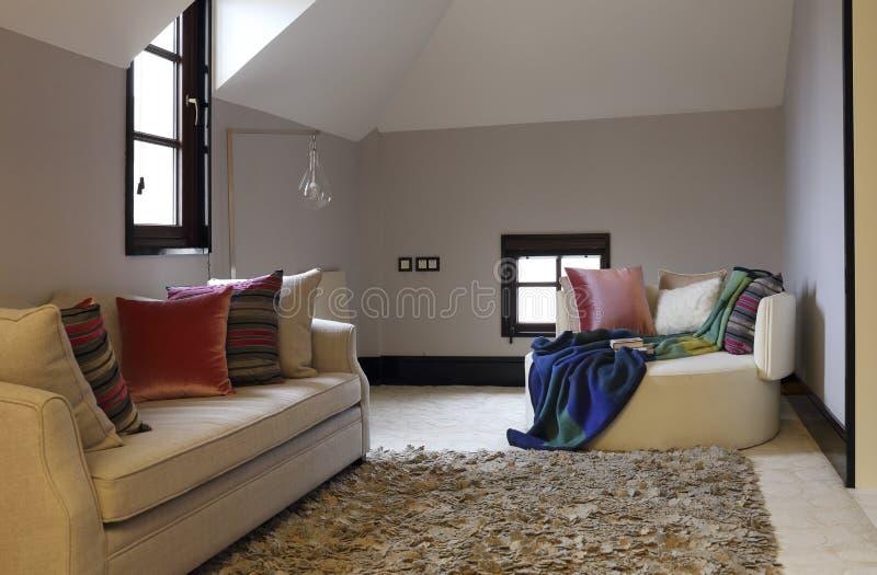Freizeitsofa und -schal im Dachbodenschlafzimmer lizenzfreies stockbild